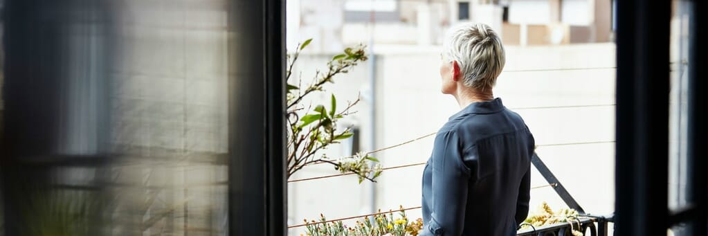 Side view of senior woman standing on balcony